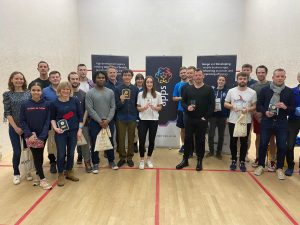 A group photo of amateur squash contestants of all genders and ages. They are posing for the photo with smiles and prizes in their hands, in front of our company banners.